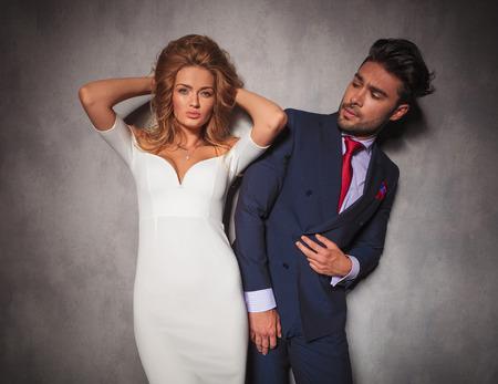 double breasted: elegante mujer sensual est� arreglando su cabello mientras est� de pie junto a su hombre, �l la est� mirando Foto de archivo