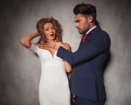 double breasted: angry fashion elegant man with his hands around his womans neck is choking her , they have problems