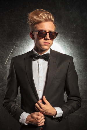 adult  male: man wearing tuxedo and bowtie pose in studio background while fixing his jacket Stock Photo