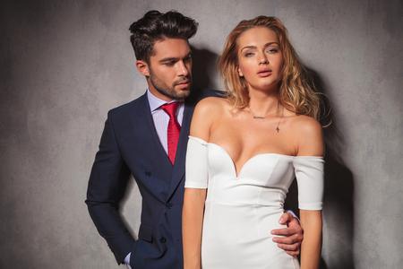 mujeres elegantes: joven hombre elegante y guapo en traje y corbata mira a su mujer rubia de vestido blanco, ella está mirando a la cámara