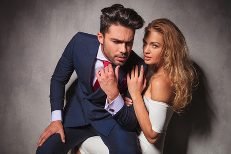double breasted: in love elegant couple, man sitting on his womans lap and looks away from the camera thinking in studio