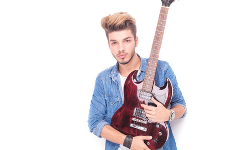 sexy guitar: serious rocker holding red electric guitar and looks at the camera on white background Stock Photo