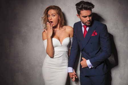 double breasted: super excited elegant woman is looking very surprised while holding her man by his hand and looks at the camera, covering her mouth with her hand