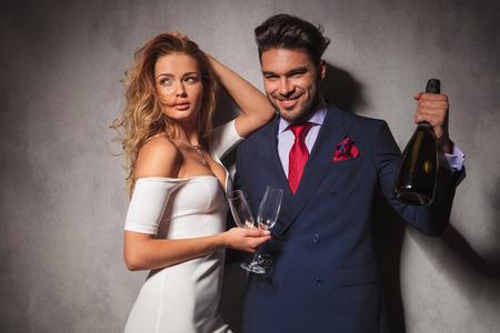 vin chaud: homme tenant une bouteille de champagne dicton acclamations avec sa femme � c�t� de lui. couple mode chaud pr�t � c�l�brer Banque d'images