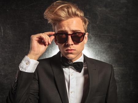 modelos hombres: Retrato de hombre joven en el estudio vistiendo esmoquin mientras la fijación de sus gafas de sol