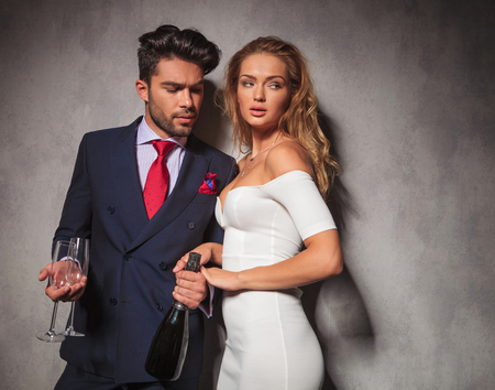 birthday suit: side view of a hot fashion couple with champagne and glasses ready to celebrate Stock Photo