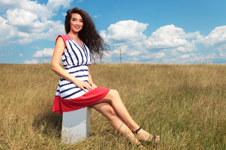 blue sky and fields: Side view picture of a gorgeous young lady sitting while smiling at the camera. Stock Photo