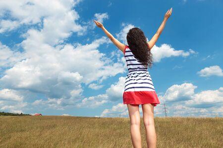 libertad: Vista trasera de una mujer atractiva joven que celebra la libertad en un campo.