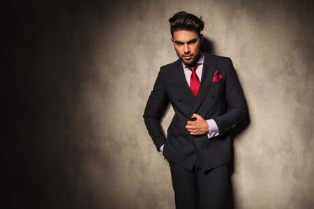 uomo rosso: Attraente giovane uomo d'affari di chiudere la giacca mentre appoggiandosi su un muro grigio.
