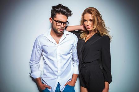時尚: 男模用雙手在口袋裡低頭而女子休息她的胳膊在他的肩上,而固定她的頭髮
