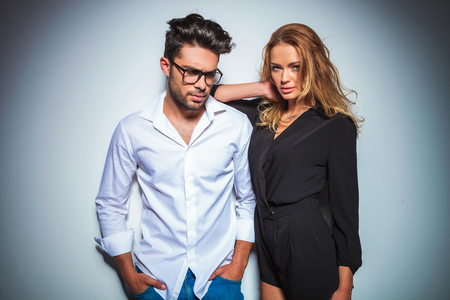 male model with hands in pockets looking down while woman resting her arm on his shoulder while fixing her hair