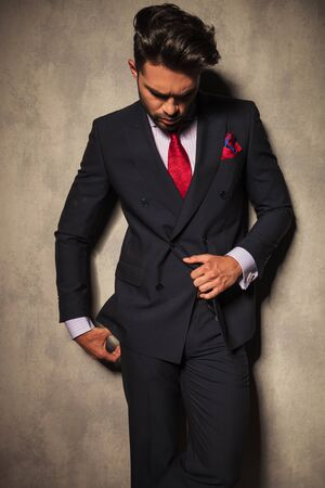 gray suit: Young business man pulling his jacket while looking down.