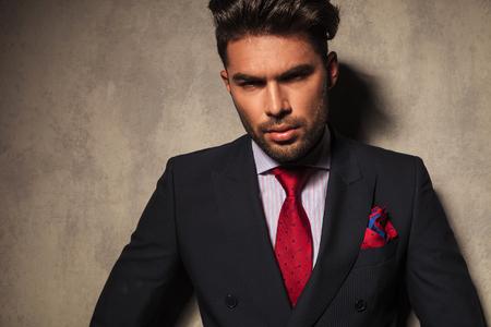 uomo rosso: Ritratto di un giovane uomo d'affari che si appoggia su un muro grigio, guardando la telecamera. Archivio Fotografico