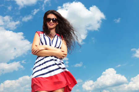 summer dress: Happy young woman holding her hands crossed while smiling at the camera. Stock Photo