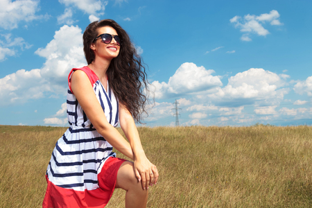 beautiful sky: Happy young woman smiling while holding both hands on her knee.