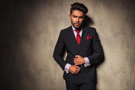 homme: Homme d'affaires Handsome fixant sa veste tout en regardant la caméra. Banque d'images