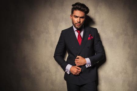 uomo rosso: Uomo bello di affari che fissa la sua giacca mentre guardando la telecamera.