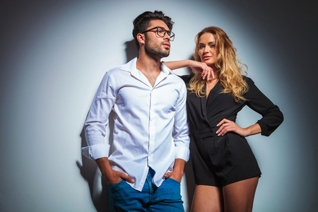 sexy couple black background: man pose looking away with hands in pockets while woman is looking at the camera with hand on waist