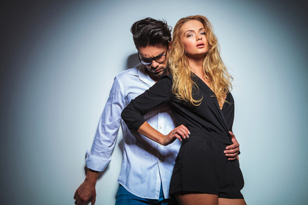 sexy couple black background: sexy woman touches her waist while her man holds her close and looks down in studio background