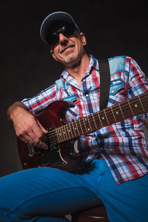 holds: old casual man having fung while playing electric guitar, wearing sunglasses and hat n studio Stock Photo