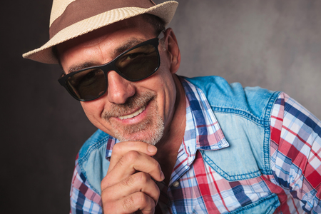 40 years old man: smiling senior casual man holding his chin and smiles to the camera, wearing a summer hat and sunglasses