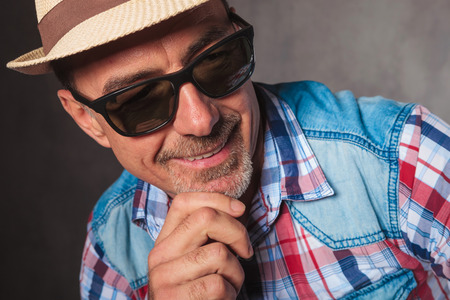 man face close up: close up picture of an old casual man with hat and sunglasees looking to side away from the camera and smiles in studio Stock Photo