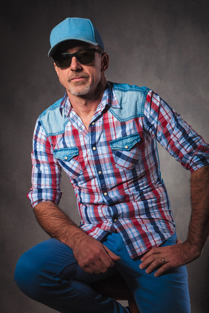man 40 50: senior trucker resting on a chair in studio, wearing a hat and sunglasses Stock Photo
