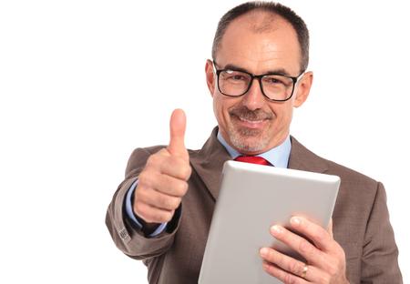 hombres maduros: feliz hombre de negocios mayor que lee buenas noticias en su ordenador de la pista de la tableta y hace los pulgares OK en señal de mano sobre fondo blanco