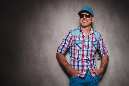 man 40 50: smiling senior casual man wearing baseball hat looking away to side in studio
