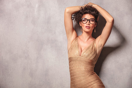 decolletage: sexy woman pose looking at the camera while holding her hair up with both hands Stock Photo