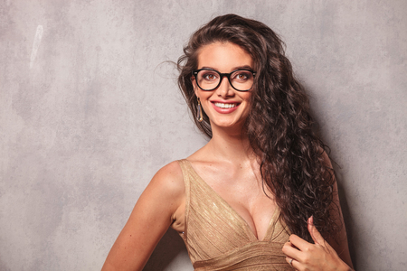 curly beautiful woman wearing glasses and smiling while arranging her hair with one hand Stock Photo