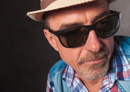 40 year old man: side view of a mature casual man looking away from the camera , wearing hat and sunglasses