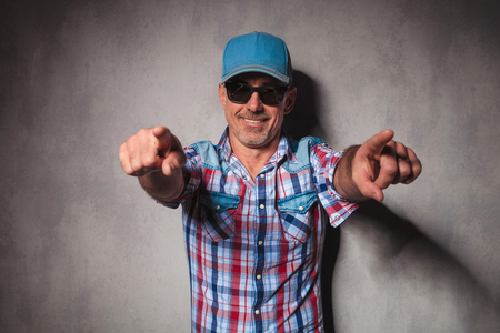cool mature casual man with trucker hat  pointing his fingers to the camera in studio Stock Photo