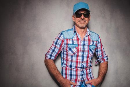 happy casual man in jeans kleding en trucker hoed lachend met de handen in de zakken Stockfoto