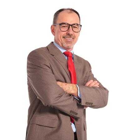 hombres maduros: viejo hombre de negocios seguro con gafas de pie con las manos cruzadas sobre fondo blanco y sonrisas