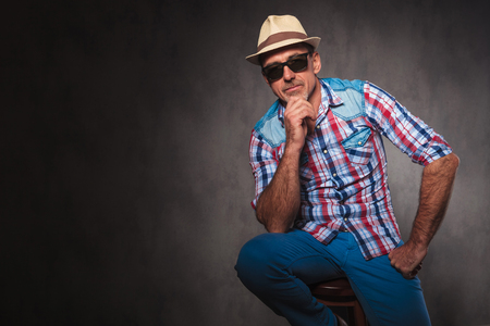 man 40 50: serious thoughtful senior casual man wearing summer hat and sunglasses looking at the camera while seated in studio