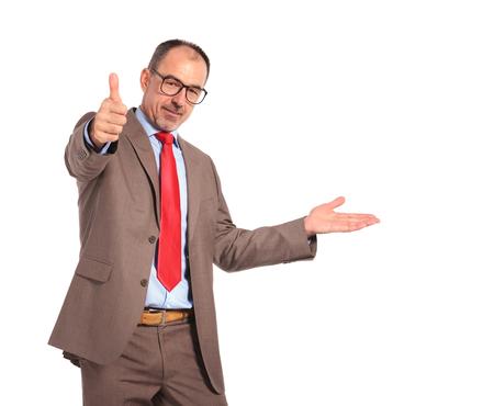 hombres maduros: Bussinessman de edad presentando y haciendo los pulgares OK en señal de mano sobre fondo blanco