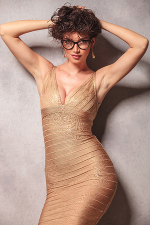 decolletage: sexy beautiful woman in golden dress poses with her hands holding her hair up
