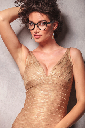 decolletage: close up with woman in golden dress posing sexy while holding her hair Stock Photo