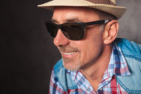 side profile picture of a happy mature man smiling, wearing summer hat and sunglasses in studio