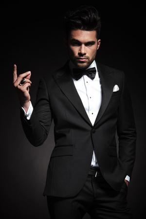 カメラを見ながら指を鳴らし若いエレガントなビジネスの男性の写真。 写真素材