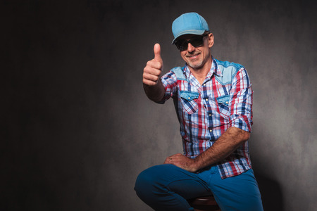 positive old casual man in trucker hat making the ok thumbs up hand sign while sitting