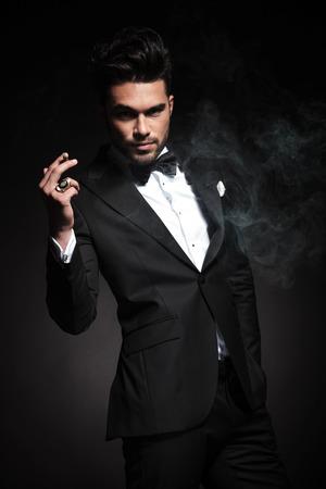 person smoking: Hombre de negocios joven que disfruta de un cigarrillo mientras mantiene una mano en el bolsillo.