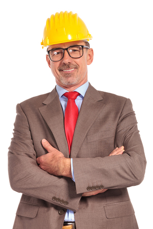 mani incrociate: felice ingegnere edile in piedi con le mani incrociate su sfondo bianco Archivio Fotografico