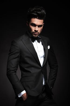 suit: Atractivo joven hombre de negocios mirando a la cámara mientras mantiene las manos en el bolsillo.