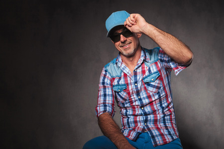 50 years old man: happy senior casual man holding his hat in a greeting pose, saying hello, in studio