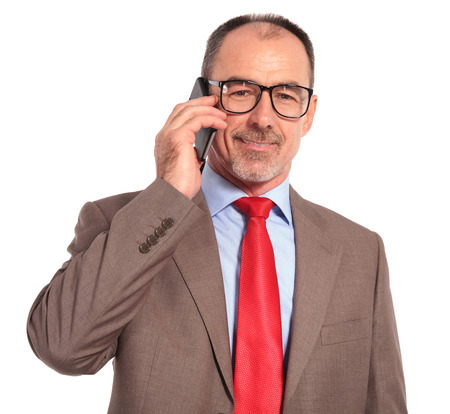 casual business: happy old businessman talking on the phone on white background
