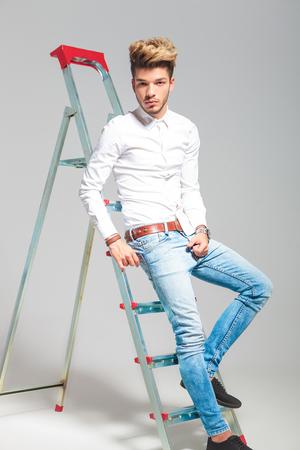 persona sentada: apuesto hombre apoyado en una escalera mientras posando en el estudio de fondo Foto de archivo