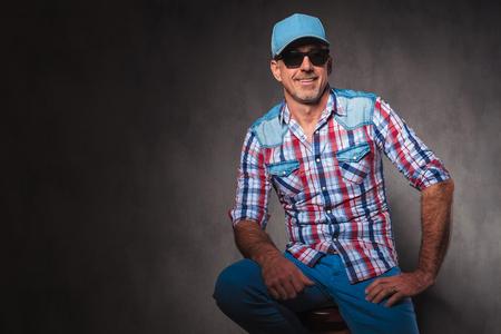 hombres maduros: casual hombre de edad confianza con el sombrero de béisbol y Sunglassed se sienta y mira a la cámara de HTE