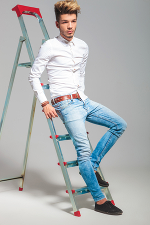 climb: young man posing in studio background while climbing on a ladder and looking away